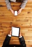 Mann und Frau, die an tragbaren Geräten arbeiten Lizenzfreies Stockfoto