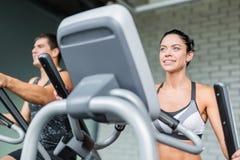 Mann und Frau, die Trainings-Maschinen in der Turnhalle verwendet stockfoto