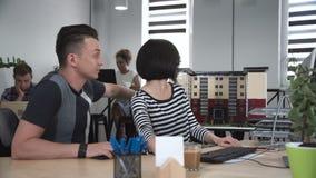 Mann und Frau, die vor Computer sich besprechen stock footage