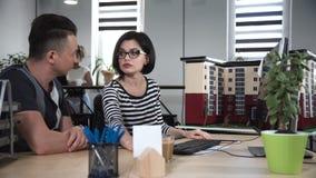 Mann und Frau, die vor Computer sich besprechen stock video footage