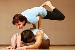 Mann und Frau, die Yogapraxis tun Stockfotografie