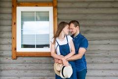 Mann und Frau, die zu Hause mit einem großen hölzernen Fenster stehen, das Ereigniskonzept einer jungen Familie, stockbilder