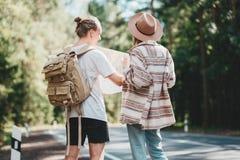 Mann und Frau, die zusammen reisen und Griff in der Handstandortkarte und Suchen Richtungs unter Bäumen im Wald lizenzfreies stockfoto