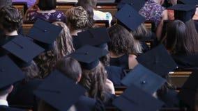 Mann und Frau graduiert in akademisches Kleideraufpassender Diplom-Gewährungszeremonie stock video footage