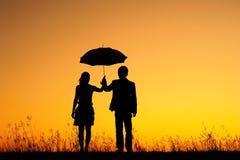 Mann und Frau halten Regenschirm im Abendsonnenuntergang an Stockbild
