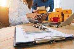 Mann und Frau im Büro ihres Geschäftson-line-Einkaufens stockbild