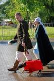 Mann und Frau im historischen Kostümweg, den der Hund, der roten Hund trägt, beschichten Lizenzfreies Stockbild