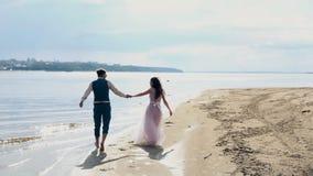 Mann und Frau, junge Leute, glückliche verheiratete erwachsene Paare, die Spaß haben und auf dem Ufer, Strand spielen stock video