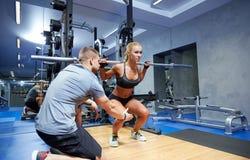 Mann und Frau mit der Stange, die Muskeln in der Turnhalle biegt Stockfoto
