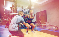 Mann und Frau mit der Stange, die Muskeln in der Turnhalle biegt Stockfotos