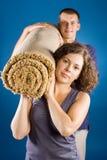 Mann und Frau mit gerolltem Teppich Stockbild