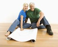 Mann und Frau mit Lichtpausen. Stockfotografie
