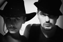 Mann und Frau mit tragenden Hüten des Schnurrbartes Stockbild