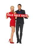 Mann und Frau mit Verkaufszeichen Stockfotos