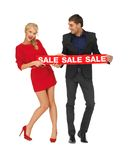 Mann und Frau mit Verkaufszeichen Stockfoto