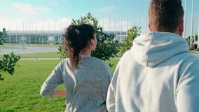Mann und Frau rütteln im Park zusammen, Rückseitenansicht stock footage