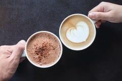 Mann und Frau ` s übergibt das Halten von Schalen des Kaffees und der heißen Schokolade mit Holztischhintergrund Lizenzfreie Stockbilder