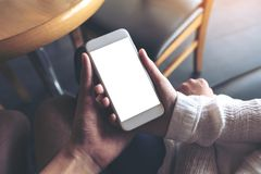 Mann und Frau ` s übergibt weißen Handy mit leerem Tischplattenschirm zusammenhalten und betrachten stockfoto