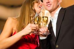 Mann und Frau schmeckende Champagne im Restaurant Stockfotos