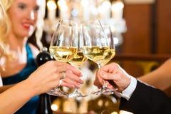 Mann und Frau schmeckende Champagne im Restaurant Stockbilder
