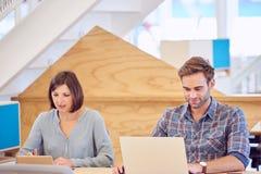 Mann und Frau stark bei der Arbeit neben einander Stockbilder