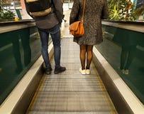 Mann und Frau steigen Rolltreppe auf Einkaufszentrum ab Füße, Schuhe, Rucksack, Geldbeutel Rückseitige Ansicht lizenzfreies stockbild