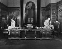 Mann und Frau am Telefon an den anderen Enden des Raumes (alle dargestellten Personen sind nicht längeres lebendes und kein Zusta Lizenzfreies Stockbild
