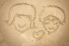 Mann und Frauen, die auf den Sand zeichnen Lizenzfreies Stockfoto