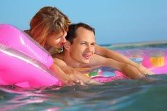 Mann und Frauen, die auf einer aufblasbaren Matratze liegen Lizenzfreie Stockbilder