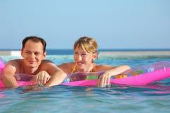 Mann und Frauen, die auf einer Matratze im Pool liegen Stockfoto