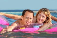 Mann und Frauen, die auf einer Matratze im Pool liegen Lizenzfreies Stockfoto