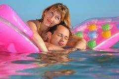 Mann und Frauen, die auf einer Matratze im Pool liegen Lizenzfreie Stockfotografie
