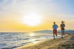 Mann und Frauen, die auf tropischem Strand bei Sonnenuntergang laufen Lizenzfreie Stockfotografie