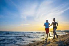 Mann und Frauen, die auf tropischem Strand bei Sonnenuntergang laufen Stockbild