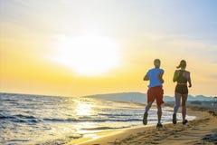 Mann und Frauen, die auf tropischem Strand bei Sonnenuntergang laufen Lizenzfreie Stockfotos