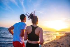 Mann und Frauen, die auf tropischem Strand bei Sonnenuntergang laufen Lizenzfreies Stockfoto