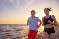 Mann und Frauen, die auf tropischem Strand bei Sonnenuntergang laufen Stockfotografie