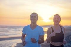Mann und Frauen, die auf tropischem Strand bei Sonnenuntergang laufen Stockfoto