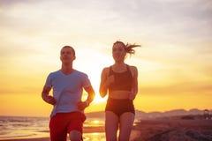 Mann und Frauen, die auf tropischem Strand bei Sonnenuntergang laufen Lizenzfreie Stockbilder