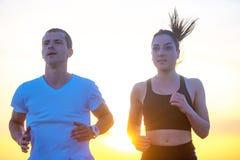 Mann und Frauen, die auf tropischem Strand bei Sonnenuntergang laufen Stockbilder