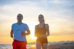 Mann und Frauen, die auf tropischem Strand bei Sonnenuntergang laufen Lizenzfreies Stockbild