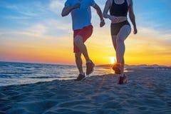 Mann und Frauen, die auf tropischem Strand bei Sonnenuntergang laufen Stockfotos