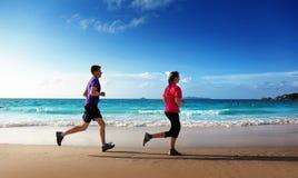 Mann und Frauen, die auf tropischem Strand laufen Stockfoto