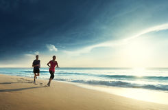 Mann und Frauen, die auf tropischem Strand laufen Stockfotografie