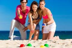 Mann und Frauen, die Boule auf Strand spielen Stockfoto