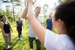 Mann-und Frauen-Geben hoch--Fünf während Freunde, die am Wald stehen stockbild