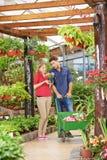 Mann- und Fraueneinkaufen in Garten-Center lizenzfreie stockbilder