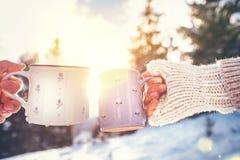 Mann- und Frauenhände in den strickenden Handschuhen, die Schalen des heißen Getränks nehmen lizenzfreies stockbild