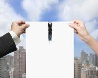 Mann- und Frauenhände, die leeres Papier mit dem Geschäftsmannhängen zerreißen Lizenzfreie Stockfotografie