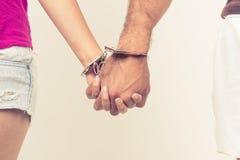 Mann- und Frauenhände zusammen mit Handschellen gefesselt Stockfotografie